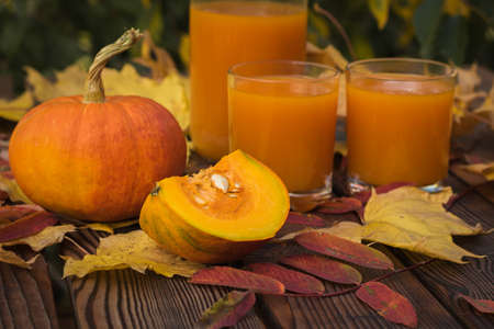 Ripe pumpkins and two glasses of pumpkin juice on a wooden table. Autumn pumpkin harvest.
