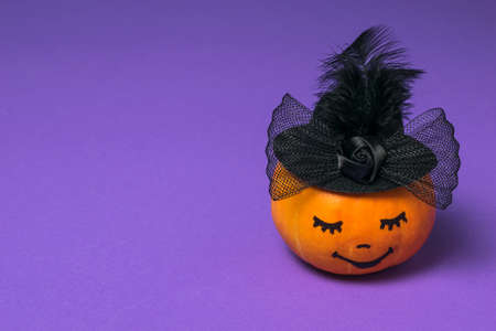 Pumpkin with a painted face in a black hat on a purple background. Halloween party.