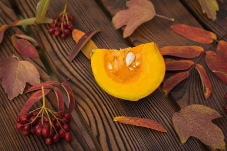 A piece of pumpkin, viburnum berries and autumn leaves on a wooden table. Autumn pumpkin harvest. 写真素材