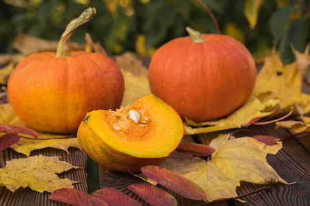 Whole and cut fruits of a ripe pumpkin on a wooden table. Autumn pumpkin harvest. 写真素材