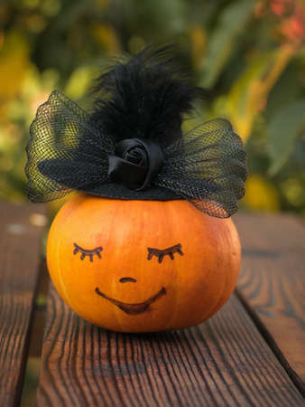 Black hat with a bow on a pumpkin with a painted face. Halloween party. 写真素材