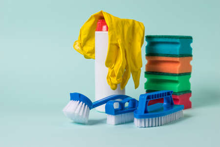 Blue brushes, foam sponges, cleaning powder and gloves on a blue background. The concept of cleaning and maintaining cleanliness.