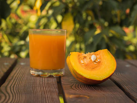 A piece of ripe orange pumpkin and a glass of juice on a wooden table. Autumn pumpkin harvest.