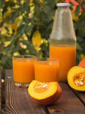 Pumpkin slices and pumpkin juice on a wooden table. Autumn pumpkin harvest. 写真素材