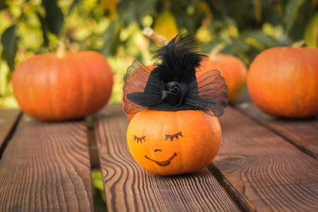 Happy pumpkin in a black hat on a wooden table. Autumn pumpkin harvest.