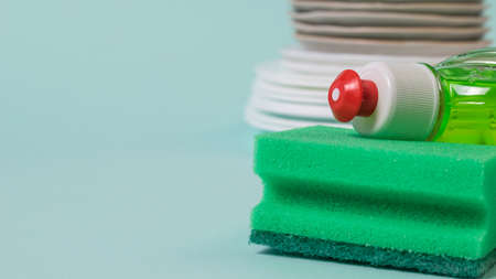Green foam sponge and green cleaning gel on the background of clean dishes. The concept of cleaning and maintaining cleanliness. 写真素材