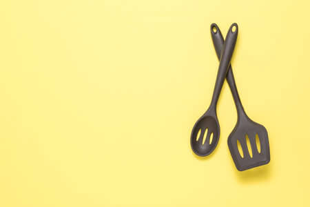 Two tablespoons of a silicone device on a yellow background. Kitchen appliances. 写真素材