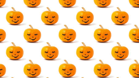 Seamless pattern of pumpkins with faces on a white background. Halloween party. 写真素材