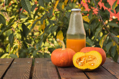 A half-filled bottle of pumpkin juice and ripe pumpkin fruit on a wooden table. Autumn pumpkin harvest.