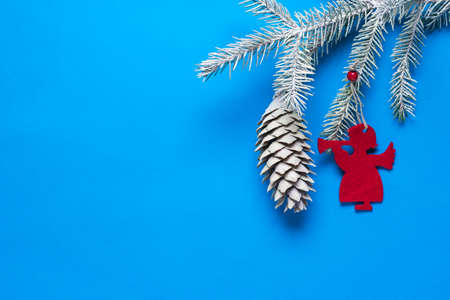 Spruce branch with a cone in the snow and decoration in the form of an angel on a blue background. Preparing for Christmas and new year.
