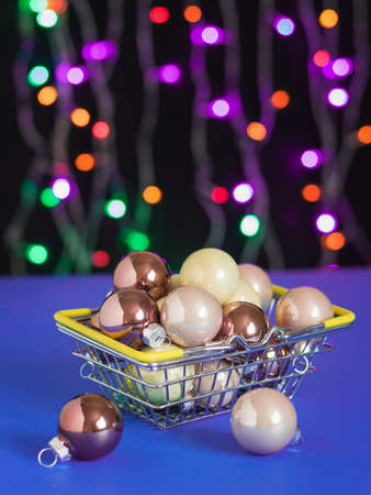 A large number of Christmas decorations in a metal basket on a blue table. Meeting of Christmas and New year.