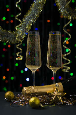 Two glasses with a bottle of champagne, streamers and tinsel on a background of colorful bokeh. Meeting of Christmas and new year.