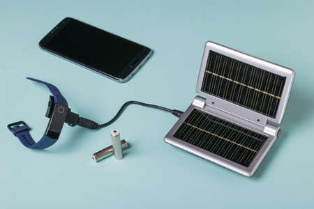 The process of charging a smart watch from solar panels. Use of solar energy. Future technology.
