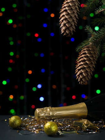 ChristmA bottle of champagne with yellow balloons under a Christmas tree on a bokeh background. Meeting of Christmas and new year. Space for text.