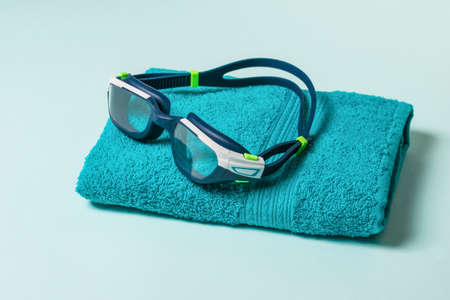 Swimming glasses on a blue towel on a blue background. Accessories for swimming in the pool.