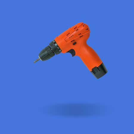 Bright orange screwdriver on a blue background. A tool with a battery.