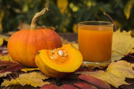 A whole pumpkin, a piece of pumpkin and a glass of pumpkin juice in autumn leaves. Autumn pumpkin harvest.