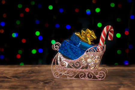 Decorative sleigh with blue gift boxes on a bokeh background. Meeting of Christmas and new year. Space for text. Stock fotó