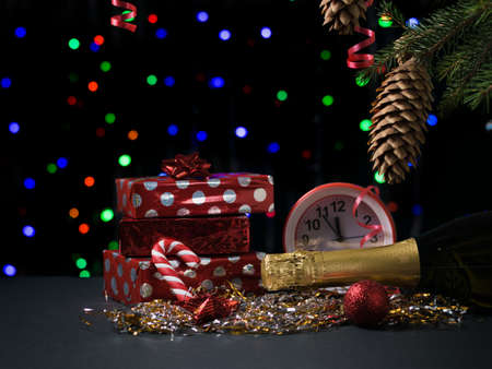 Gifts, champagne, watches and sweets on a bokeh background. Meeting of Christmas and new year. Space for text.