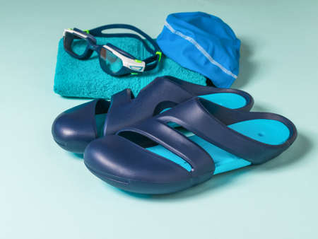 Slates for the pool, glasses, hat and towel on a blue background. Accessories for swimming in the pool. Stock fotó