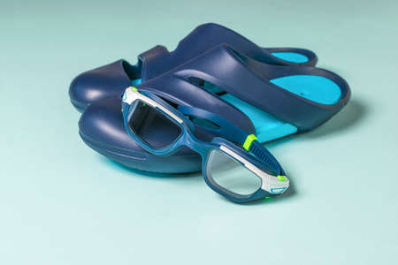 Goggles and flip-flops for the pool on a blue background. Accessories for swimming in the pool.