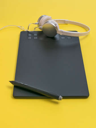 Modern graphic tablet with headphones on a yellow background. The tools of a designer. Stock fotó