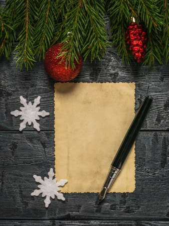 A pen and a sheet of old paper on a wooden table with spruce branches. A letter requesting a gift. Stock fotó