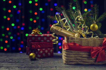 Sweets, gift boxes and champagne on a bokeh background under a Christmas tree. Meeting of Christmas and new year. Space for text.