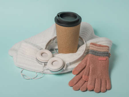 Coffee Cup, gloves, scarf and headphones on a blue background. Winter mood.