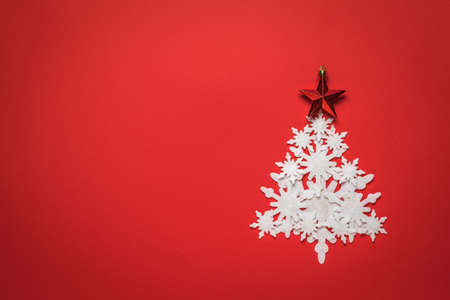 Christmas tree made of white paper snowflakes with a red star on a red background. Christmas and new year holidays. Place for text.