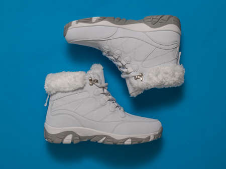 Top view of white women's winter sneakers on a blue background. Sports shoes for winter.