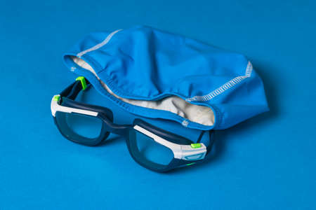 Blue swimming glasses and a cap on a blue background. Accessories for swimming in the pool. Stock fotó