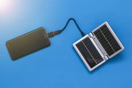 The smartphone is charged from a device with solar panels. Use of solar energy. Future technology. Stock fotó