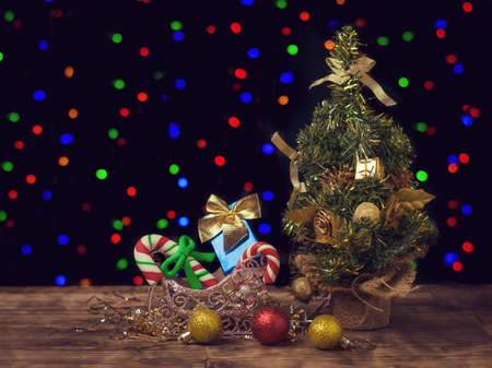 Christmas tree, gifts and decorations on the wooden floor on the background of bokeh. Christmas and New year celebrations. Space for text.
