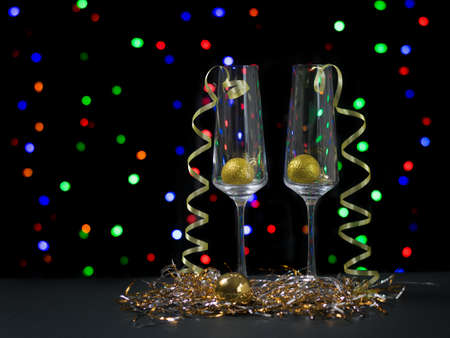 Two glasses with Christmas decorations on the background of colorful bokeh. Meeting of Christmas and new year.