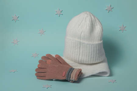 Knitted gloves, hat and scarf on a blue background with snowflakes. Fashionable winter accessories.
