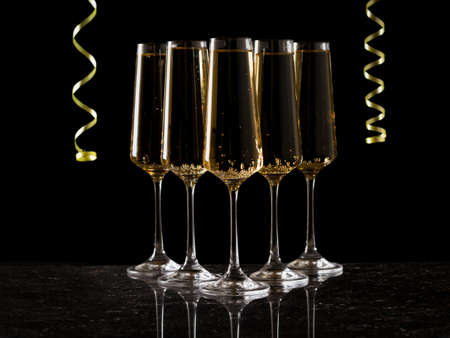 Five glasses of sparkling wine and a yellow serpentine on a black background. A popular alcoholic drink.