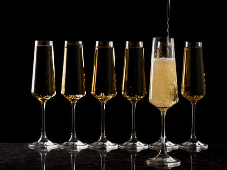 Filling a glass with sparkling wine against the background of a number of other glasses. A popular alcoholic drink. Stock fotó