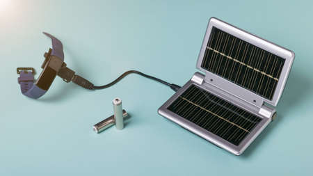 The process of charging a smart watch from the energy of sunlight. Use of solar energy. Future technology.