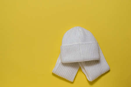 White hat and scarf on a bright yellow background. Autumn mood. Stock fotó