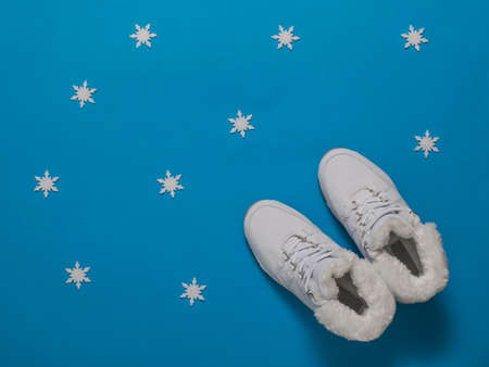Winter women's sneakers insulated with fur on a blue background. Sports shoes for winter. Stock fotó