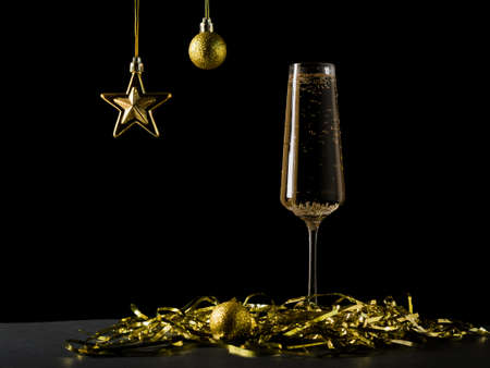 Glass with sparkling wine and decorations in yellow on a black background. A popular alcoholic drink.