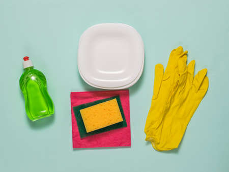 Set for washing dishes and clean white dishes on a blue background. Homework. Washing dishes by hand.