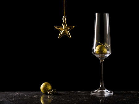 Champagne glass and Christmas decorations on a black background. Christmas eve.