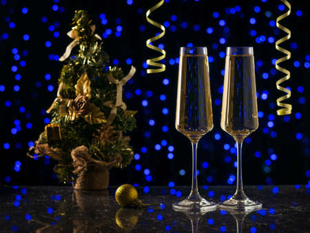 Two glasses of sparkling wine and a Christmas tree on blue bokeh