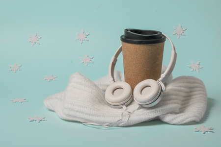 A Cup of coffee wrapped in a scarf on a blue background with snowflakes. Winter mood.