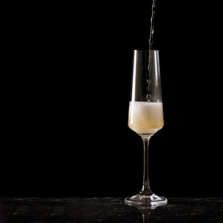 Filling a glass with champagne on black Stock fotó