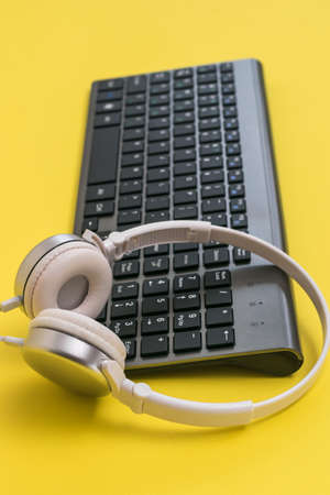 Classic wireless keyboard and white headphones on a yellow background. Peripheral devices for the computer.