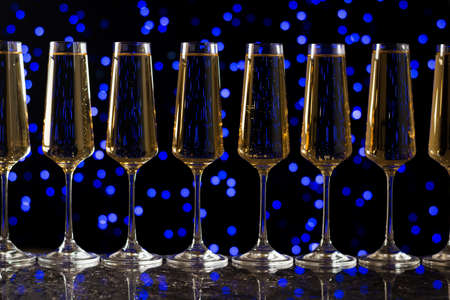 Lots of sparkling wine glasses on a blue bokeh background. A popular alcoholic drink.