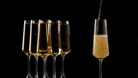 Filling a glass with champagne of five full glasses.